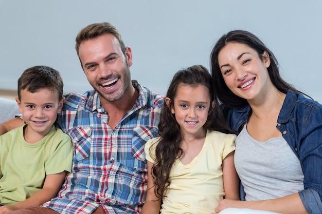 Família sentada no sofá e sorrindo