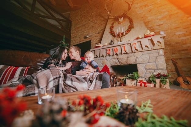 Família sentada no sofá revestido com um cobertor e visto a partir das decorações de natal da mesa de madeira