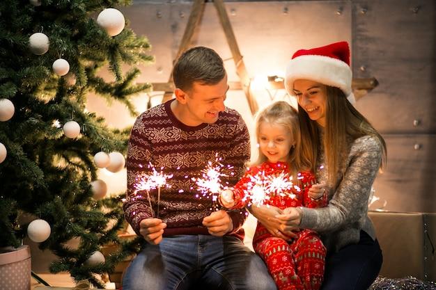 Família sentada pela árvore de natal com luzes de bengala