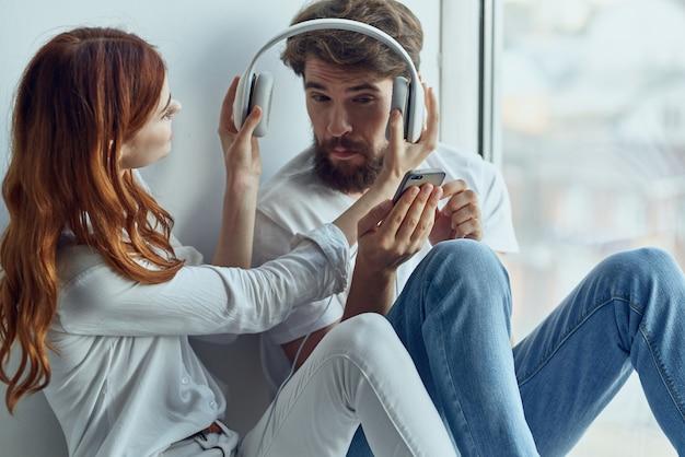 Família sentada perto da janela com fones de ouvido, tecnologia de romance e alegria