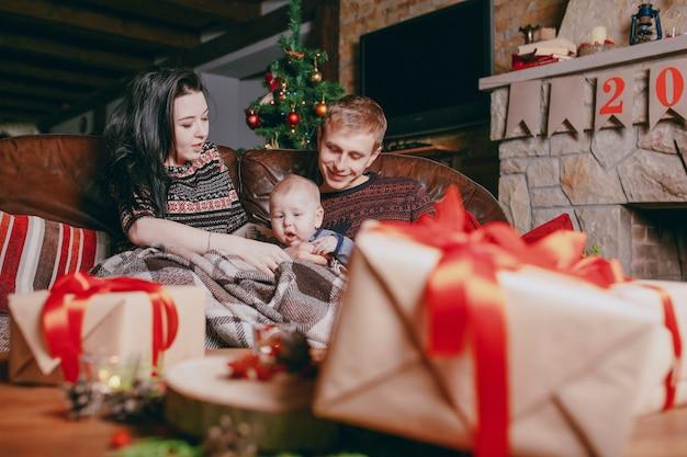 Família sentado em um sofá visto através presentes castanhos com fitas vermelhas