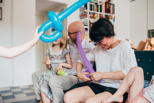 Família sentado sofá interior brincando com brinquedos de balão