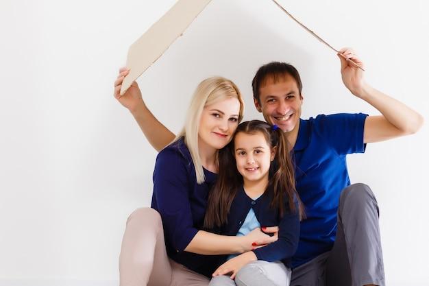 Família sentados juntos e fazendo o sinal de casa. vida normal com coronavírus. estilo de vida covid-19. quarentena de proteção contra vírus esterilidade em casa junto com o símbolo do coração