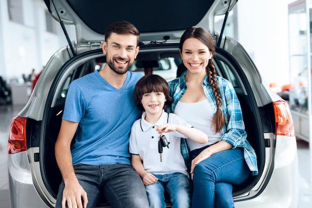 Família sentou-se na mala do carro e sorrindo.