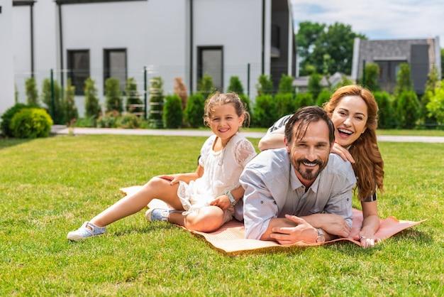 Família simpática e positiva deitados no chão juntos enquanto passam o tempo ao ar livre