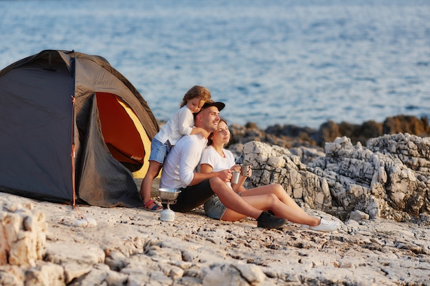 Família sincera amigável que descansa na praia rochosa perto da barraca.
