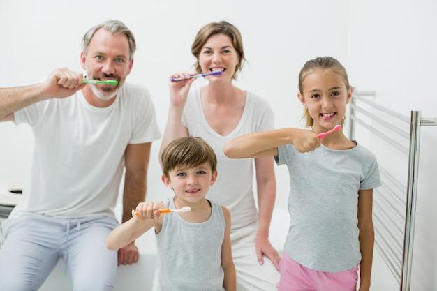 Família sorridente a escovar os dentes com escova de dentes em casa