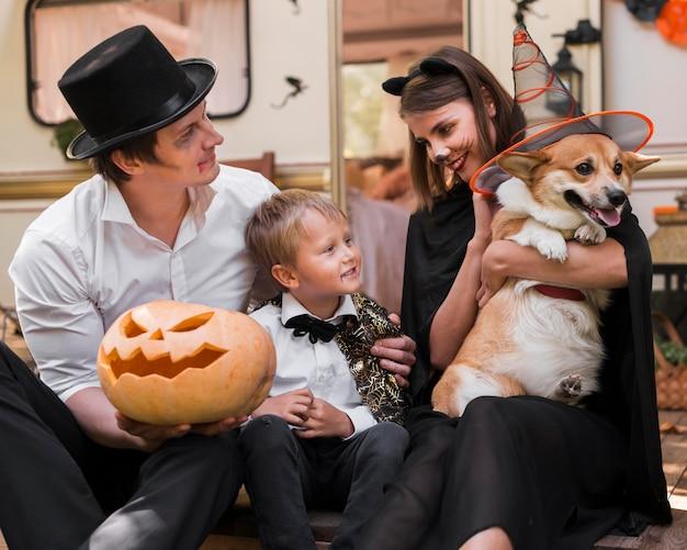 Família sorridente com cachorro em plano médio