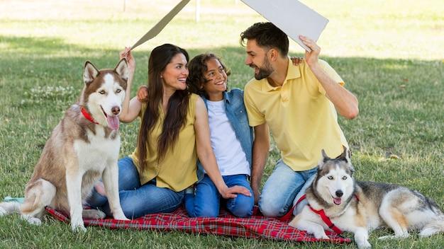 Família sorridente com cachorros passando um tempo juntos no parque