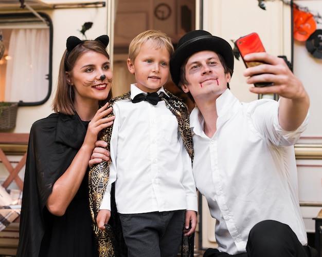 Família sorridente com foto média tirando selfie