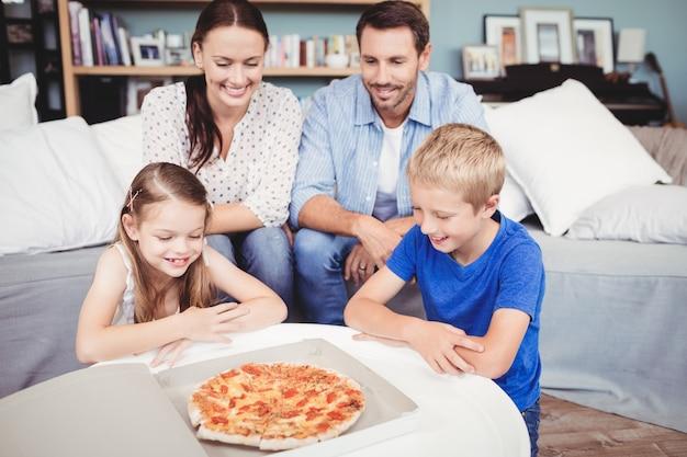 Família sorridente com pizza na mesa