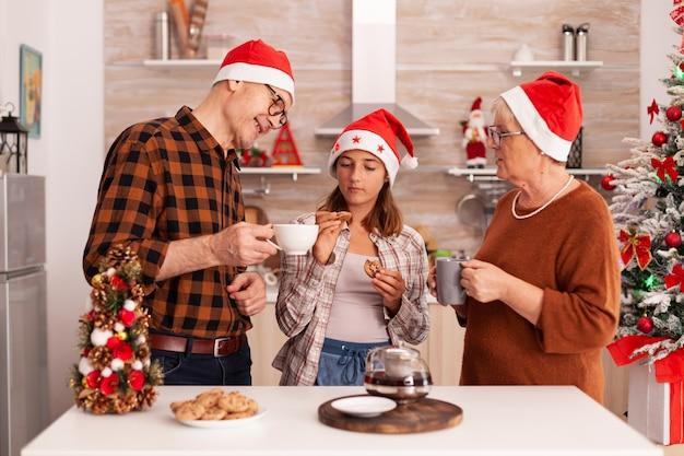 Família sorridente comemorando a temporada de natal juntos na culinária de natal decorada