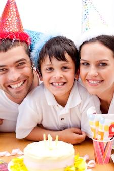 Família sorridente comemorando o aniversário do filho