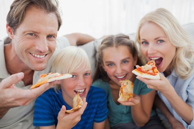 Família sorridente comendo pizza