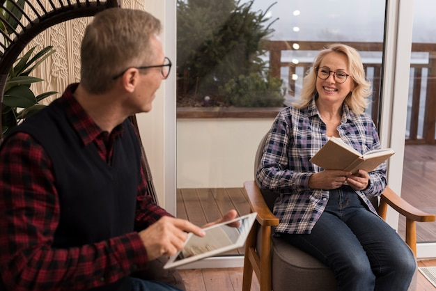 Família sorridente em casa lendo e olhando para tablet