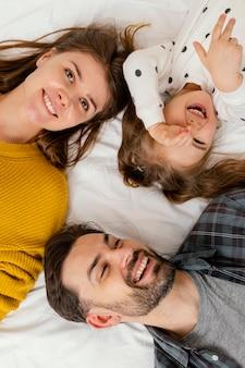 Família sorridente em close-up na cama