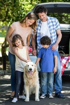 Família sorridente em pé na frente de um carro