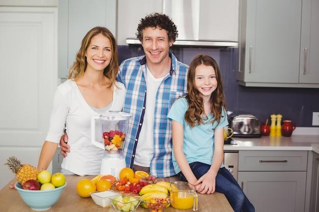 Família sorridente em pé na mesa com frutas