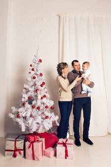 Família sorridente feliz perto da árvore de natal
