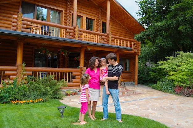 Família sorridente feliz perto da casa de madeira