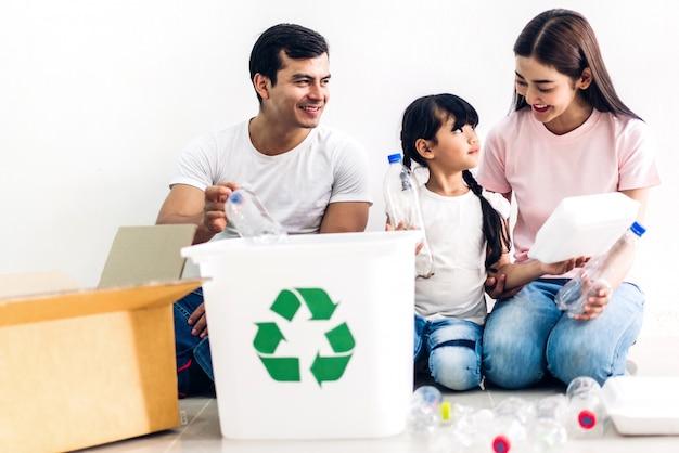 Família sorridente feliz se divertindo colocando garrafas de plástico vazias de reciclagem e papel na caixa de reciclagem