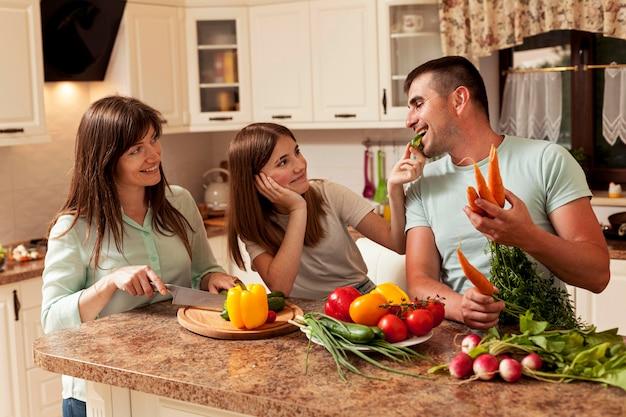 Família sorridente na cozinha preparando comida
