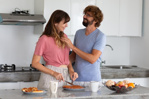 Família sorridente na cozinha preparando e degustando comida