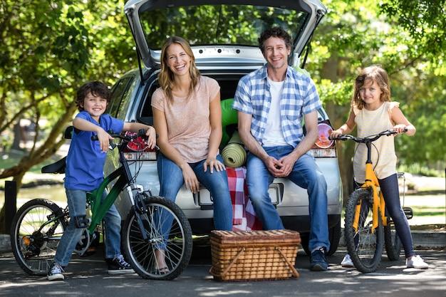 Família sorridente na frente de um carro