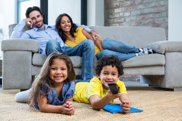 Família sorridente na sala de estar com televisão