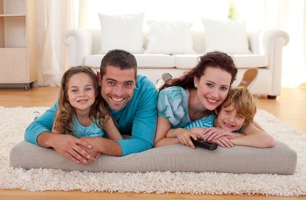 Família sorridente no chão na sala de estar