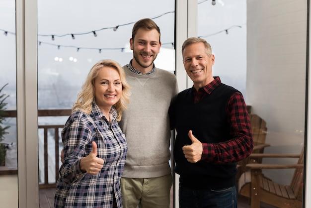 Família sorridente posando com filho e polegares para cima