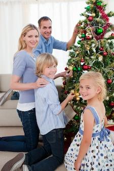 Família sorridente que decora uma árvore de natal