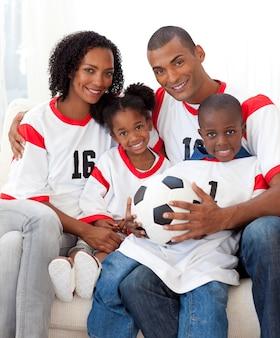 Família sorridente segurando uma bola de futebol
