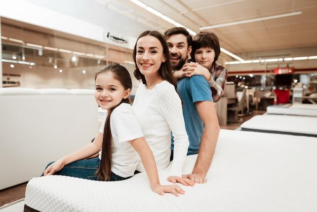 Família sorridente, sentada na cama na loja de colchão