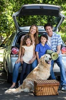 Família sorridente, sentado no espaço de bagagem