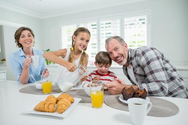 Família sorridente tomando café da manhã na cozinha