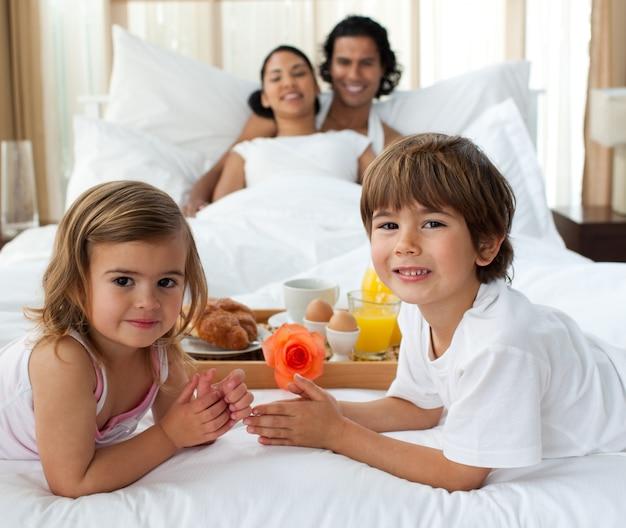Família sorridente tomando café da manhã no quarto