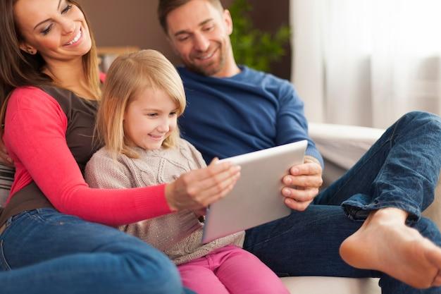 Família sorridente usando tablet digital em casa