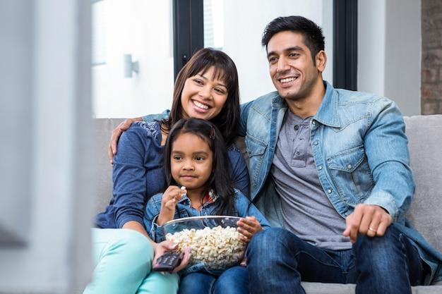 Família sorrindo comendo pipoca enquanto assistia tv