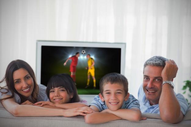 Família sorrindo na câmera com a copa do mundo mostrando na televisão