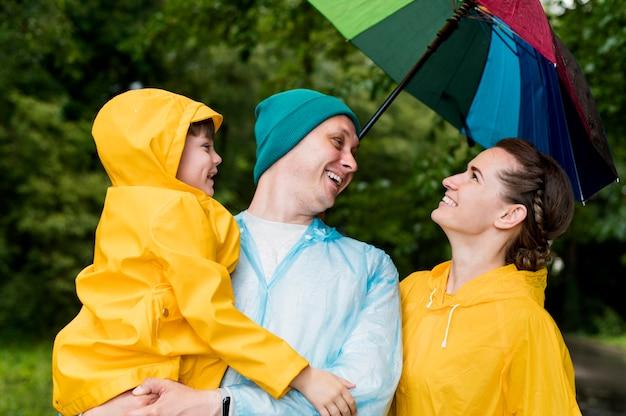 Família sorrindo sob seu guarda-chuva