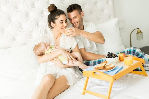 Família tendo café da manhã na cama