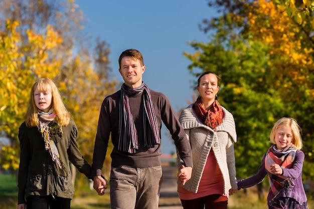 Família tendo caminhar na frente de árvores coloridas no outono