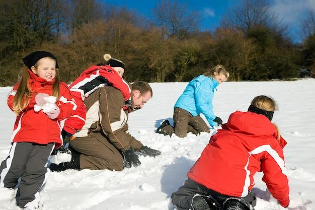 Família tendo uma luta de bolas de neve