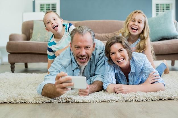 Família tirando uma selfie enquanto deitados juntos no tapete