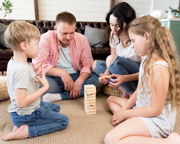 Família tocando jenga na sala de estar
