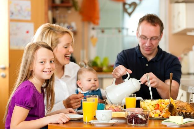 Família tomando café da manhã na cozinha de sua casa