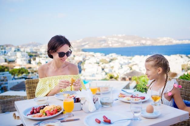 Família tomando café da manhã no café ao ar livre com uma vista deslumbrante sobre a cidade de mykonos. adorável menina e mãe bebendo suco fresco e comendo croissant no terraço do hotel de luxo