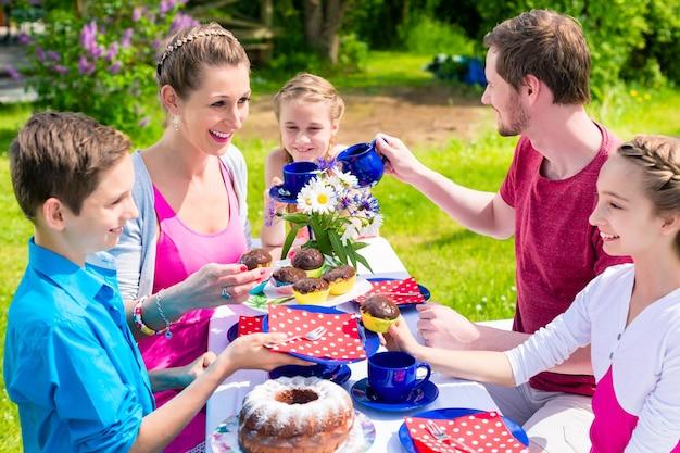 Família tomando café e bolo no jardim em frente à casa em uma mesa ao ar livre