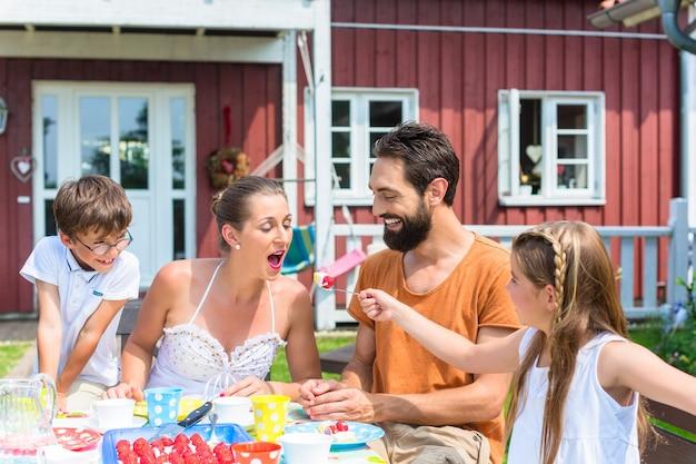 Família tomando café no jardim, comendo bolo de morango
